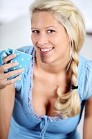 blond woman drinking a cup of coffee