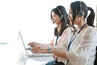 Businesswomen on headsets, Tokyo Prefecture, Honshu, Japan