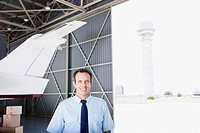Worker standing with airplane in hangar