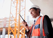 Construction worker talking on walkie talkie on construction site (thumbnail)