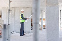 Construction worker holding blueprint on construction site
