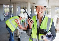 Businesswoman talking on walkie talkie on construction site