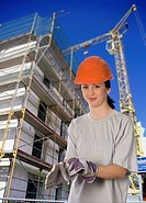 female building worker wearing safety helmet and gloves on a building site