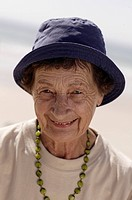 elderly woman wearing a sunhat smiling delightfully