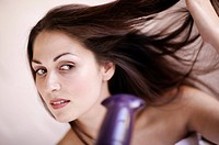 woman blow_drying her dark long hair