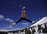skier jumping up in the air and doing a split
