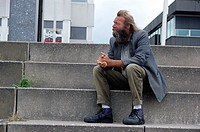 A man with beard and mustage sits on stairs.