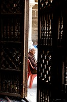 man sitting outside mosque, islamic cairo, cairo, egypt