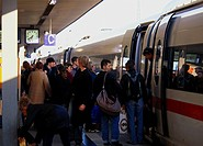 plenty of people stepping out of a train at a railway station