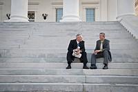 Businessman sitting on steps talking