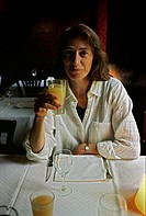 Woman with a glass of juice in a restaurant.