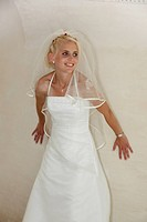 bride posing in front of white wall