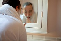 Man shaving in bathroom mirror