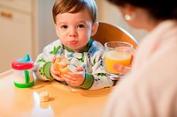 Baby boy sitting in high chair having breakfast