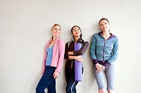 Three women in dance studio standing by wall