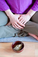 Woman sitting cross legged with teacup on floor (thumbnail)
