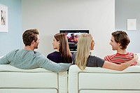 Two couples watching television