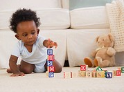 African American baby playing on floor with blocks