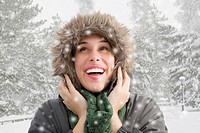Mixed race woman in fur hood watching snow fall