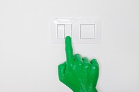 A green hand switching on a light