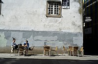 Two girls sitting in a terrace in the old city of Santiago de Compostela. Galicia, Spain