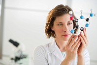 USA, New Jersey, Jersey City, woman in laboratory holding molecule model