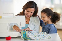 USA, New Jersey, Jersey City, mother with daughter 6_7 using sewing machine