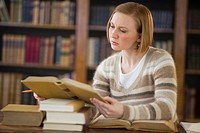 USA, New Jersey, Jersey City, woman reading book in library