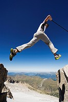 Hiker jumping across a gap in the rocks, Pico de Aneto, the highest peak in the Pyrenees, Spain, Europe