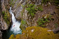 A male kayakers drops a 30 ft waterfall on Sand Creek, Galloway, British Columbia, Canada