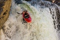 A male kayaker paddles off Raft Falls, Clearwater, British Columbia, Canada