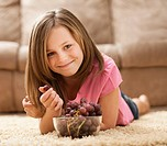 USA, Utah, Lehi, Portrait of girl 10_11 lying on rug, eating red grapes