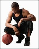 Studio shot of man with basketball crouching