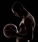 Studio shot of shirtless man holding basketball
