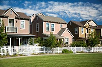 Row of homes in housing community with white picket fence