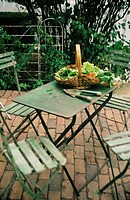 Patios: Puritan bricks from city street. green painted european cafe furniture table / chairs , gardening hand tools, basket of fresh picked lettuce a...