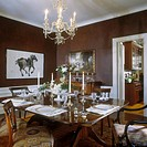 DINING ROOM _ Formal fruitwood table. Dark brown sponge paint, white molding and trim, artwork, Chinese horse in black and white, formal place setting...