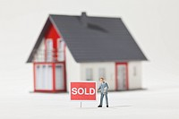 A miniature real estate agent figurine standing next to a SOLD sign