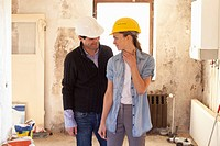 A couple standing in their house that´s under renovation