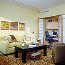 OFFICES_HOMES _ Den with computer area behind folding fabric screens, light yellow walls, yellow stripped sofa, oriental area rug.