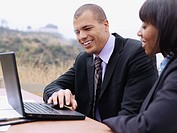 A businessman and a businesswoman using a laptop together