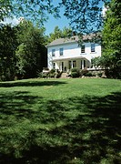 EXTERIORS: Two story single family stucco 1840 farmhouse in a Georgian Colonial style, front porch with concrete steps, large lawn in front, mature tr...