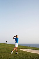 A young woman playing golf by the sea, Gran Canaria, Spain.