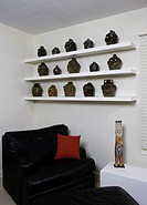 BEDROOM: Contemporary mixed with antique folk art face jugs, black leather with red pillow,