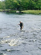 A man fishing in a river, Sweden.