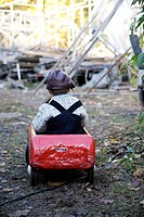 Boy in a red pedal car, Sweden.