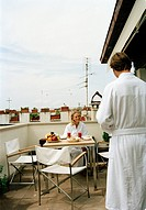 Couple having breakfast on a terrace, Italy.