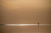 Landscape with horizon line illuminated by sunlight with silhouette of yacht