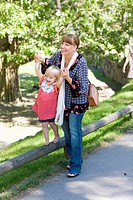 Mother assisting daughter walking on railing at zoo