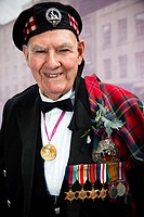 Tom Gilzean, 90 years old ex soldier, in highland dress and wearing his military medals, collecting for charity in Edinburgh Scotland